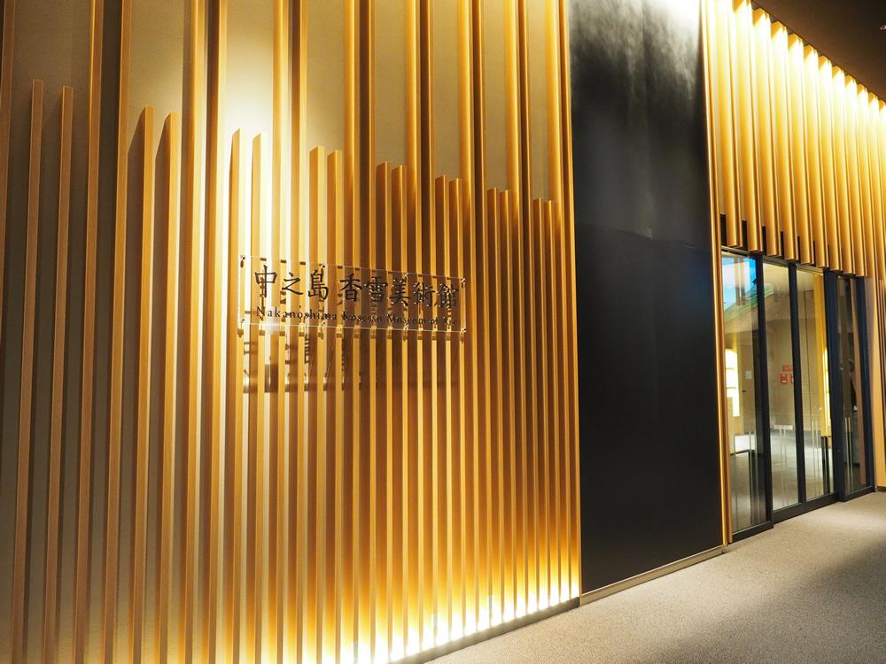 中之島香雪美術館エントランス。木目のデザインと土壁が、近代建築と和の世界観を融合した独自の空間を生み出します。