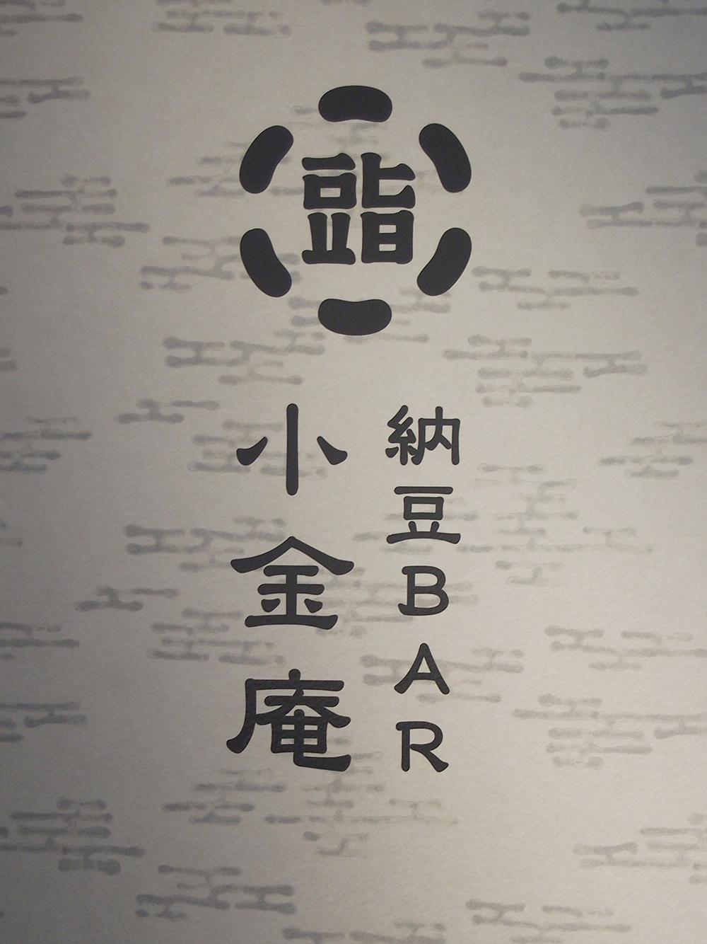 「小金庵」のロゴマークは、「豆」ヘンに、「旨」のツクリで 「なっとう」と読みます。創業者であるお父さまの考案された マークだそうです。