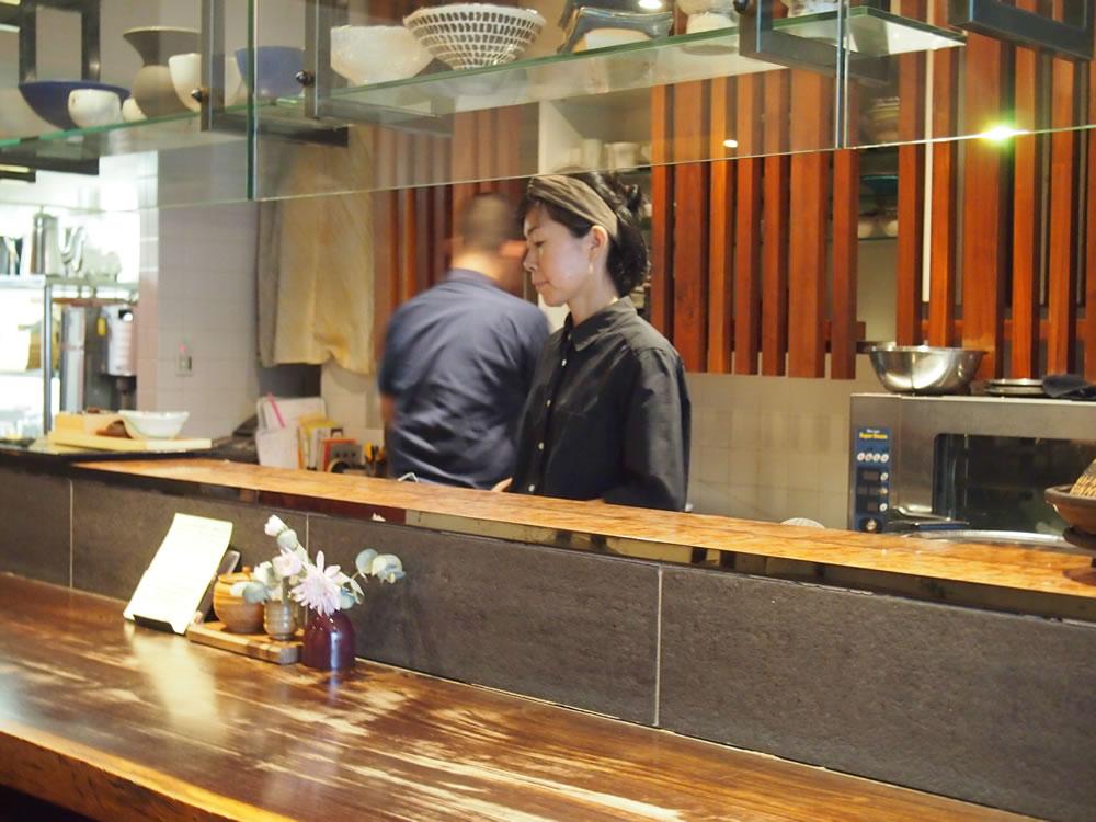 調理中の栄田さん。後ろにいらっしゃるのは、ご主人の栄田健二さん。二人三脚でお店を切り盛りしています。