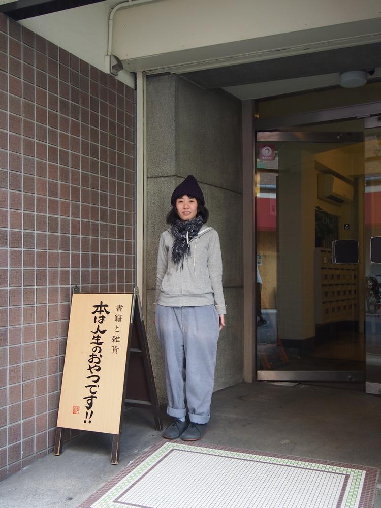 ビルの1階に置かれた看板と、坂上さん。坂上さんのやさしい雰囲気が、そのままお店全体に行き渡っているようです。
